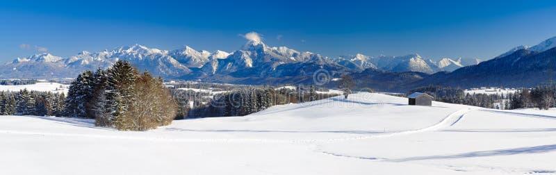 Breite Panoramalandschaft im Bayern mit Alpenbergen und im See im Winter lizenzfreie stockbilder