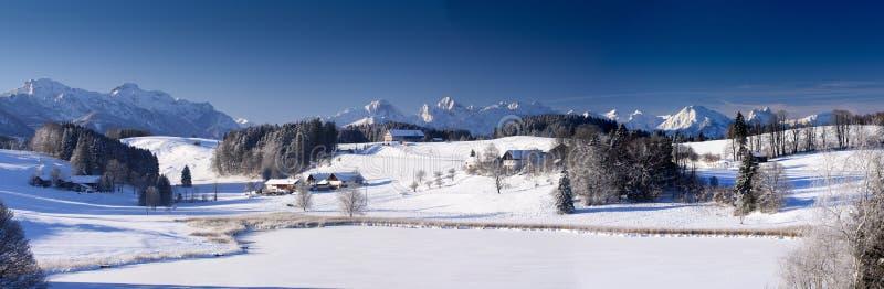 Breite Panoramalandschaft im Bayern mit Alpenbergen und im See im Winter stockfotografie