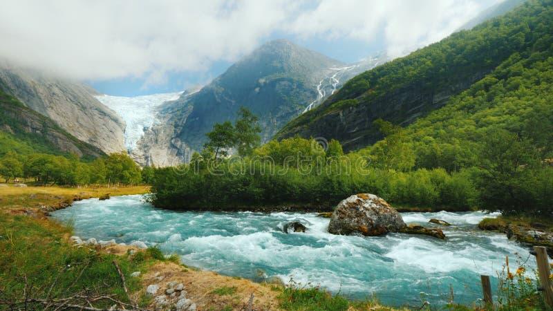Breiter Linsenschuß: Briksdal-Gletscher mit einem Gebirgsfluss im Vordergrund Die erstaunliche Beschaffenheit von Norwegen stockfotos