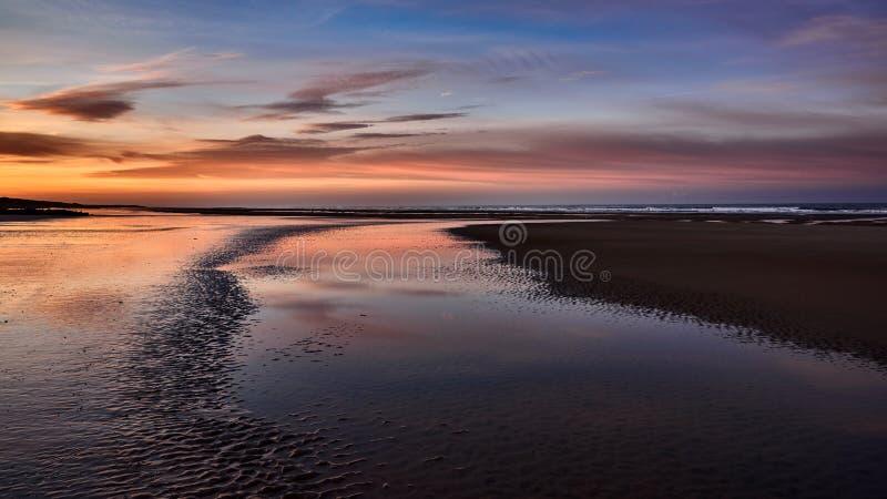 Breiter Schuss der schönen Küste des Meeres mit dem erstaunlichen bewölkten Himmel während der goldenen Stunde stockfoto