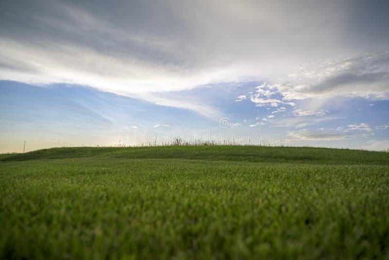 Breiter Schuss eines schönen grünen Feldes mit dem Überraschen von großen Wolken im blauen erstaunlichen Himmel lizenzfreies stockfoto