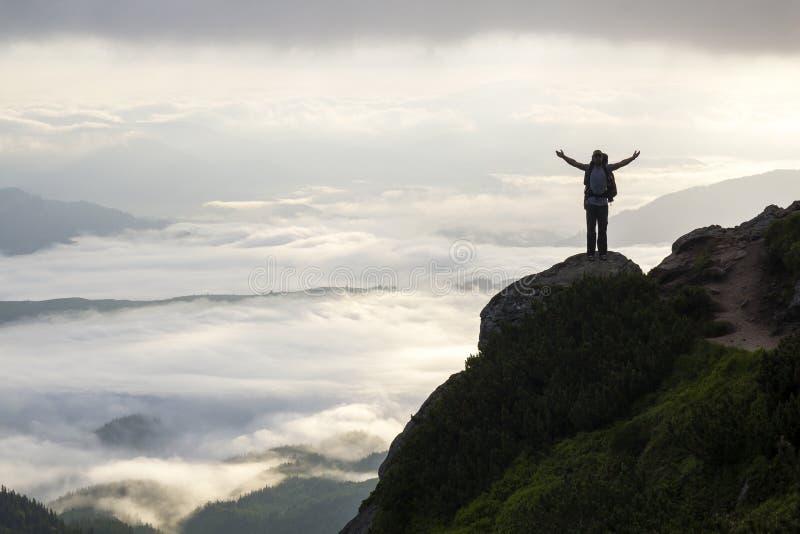 Breites Bergpanorama Kleines Schattenbild des Touristen mit Rucksack auf felsigem Berghang mit angehoben ?berreicht das bedeckte  stockfotografie