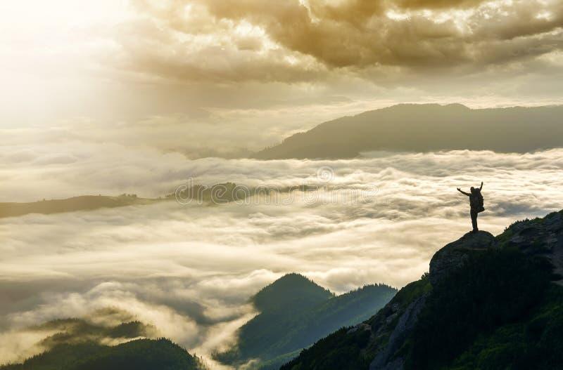 Breites Bergpanorama Kleines Schattenbild des Touristen mit Rucksack auf felsigem Berghang mit angehoben ?berreicht das bedeckte  lizenzfreie stockbilder