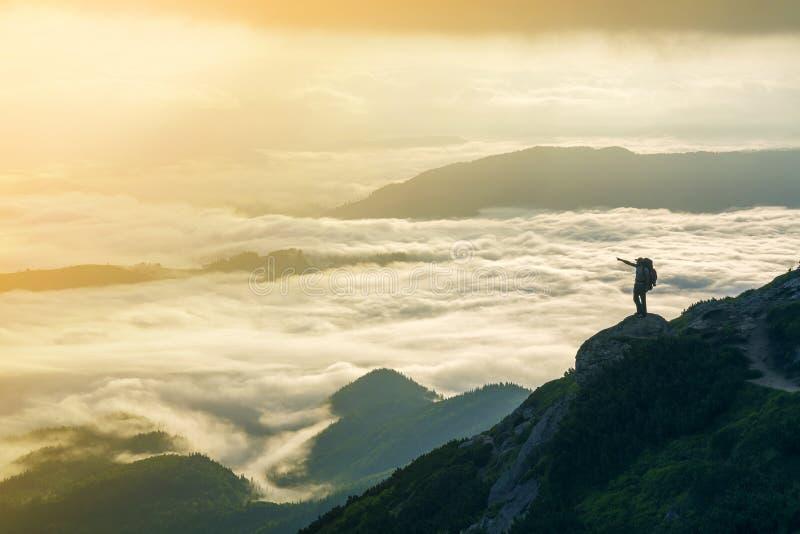 Breites Bergpanorama Kleines Schattenbild des Touristen mit Rucksack auf felsigem Berghang mit angehoben ?berreicht das bedeckte  lizenzfreie stockfotos