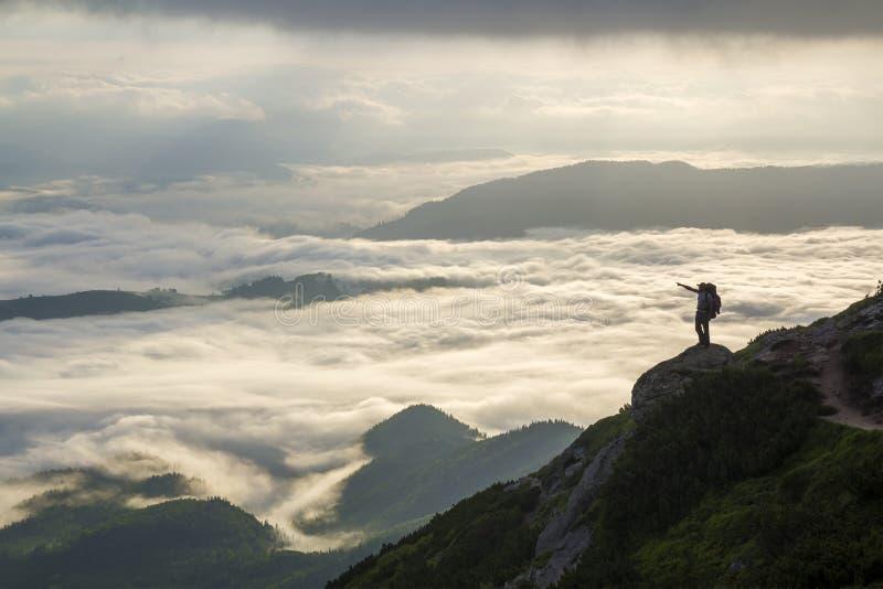 Breites Bergpanorama Kleines Schattenbild des Touristen mit Rucksack auf felsigem Berghang mit angehoben ?berreicht das bedeckte  stockbilder