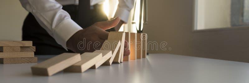 Breites Panorama eines Geschäftsmannes, der den Domino-Effekt stoppt stockfotos