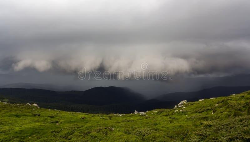 Breites Sommerbergpanorama vor Gewitter Dunkles niedriges grünes grasartiges felsiges übermäßigtal der Regenwolken und entfernter stockfoto