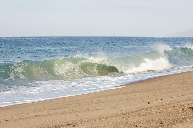 Brekende buisgolf op zandig strand met schuimende terugslag, open uitgestrektheid van oceaan stock afbeelding