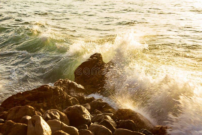 Brekende golf met schuim op rotsachtige kust, die op rotsen bespatten royalty-vrije stock foto