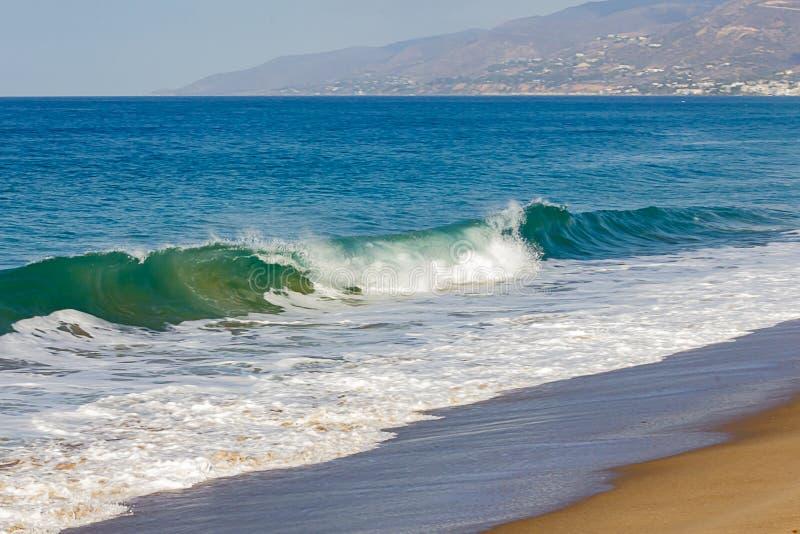 Brekende golf op oceaan, met terugslag op open oceaan met horizon, zandig strand stock fotografie