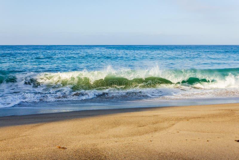 Brekende golf op oever met terugslag, backspray, met zandig strand stock afbeelding