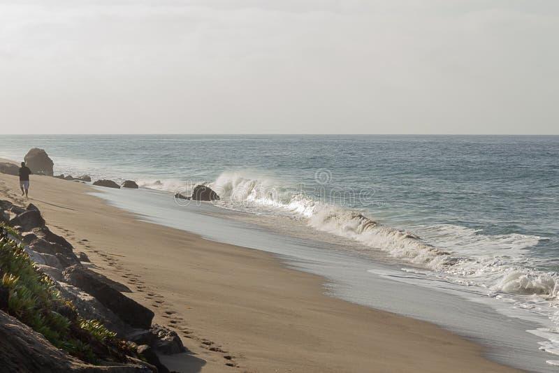 Brekende golf op zandig strand, mens die verlatend voetafdrukken in afstand lopen royalty-vrije stock afbeelding