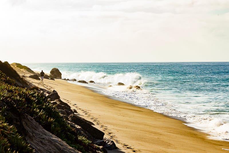 Brekende golf op zandig strand, mens die verlatend voetafdrukken in afstand lopen royalty-vrije stock fotografie