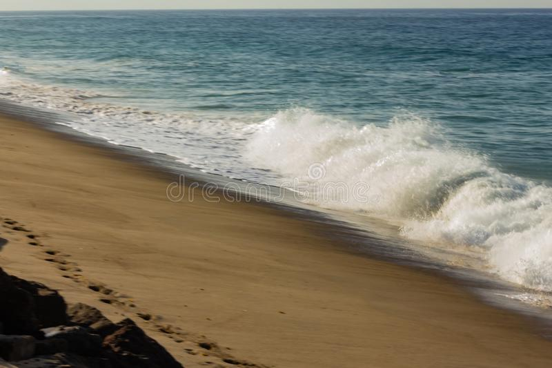 Brekende golf op zandig strand, met terugslag, voetafdrukken en rotsen royalty-vrije stock foto's