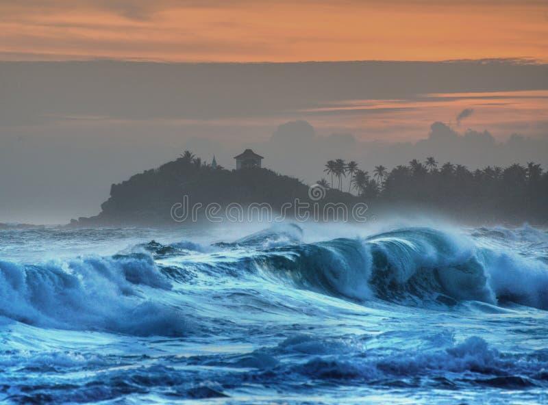 Brekende golven met tempel en palmen in silhouet stock afbeeldingen