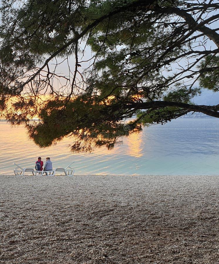 Brela 克罗地亚- 2019年6月5日:一对移动的夫妇、男人和妇女坐太阳懒人由海在晚上 库存照片