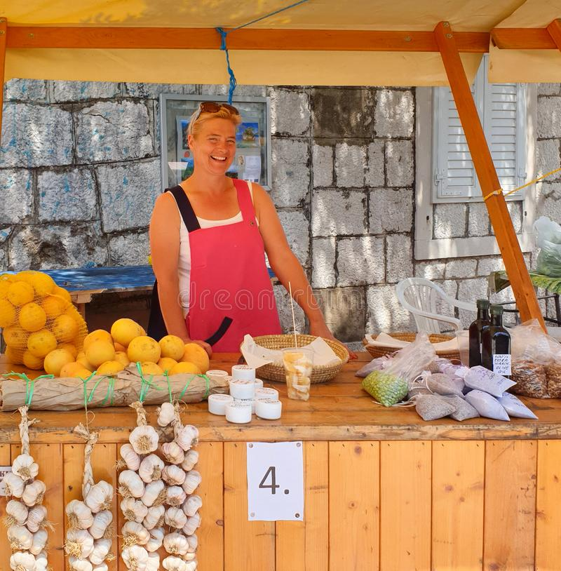 Brela 克罗地亚- 2019年6月25日:公平地,美丽的微笑的妇女在柜台后站立并且卖季节性水果和蔬菜 图库摄影