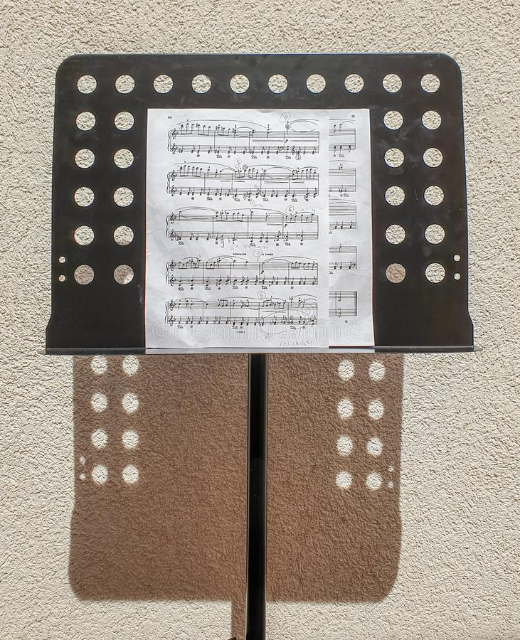 Brela 克罗地亚- 2019年6月5日:在一条腿的一个黑乐谱架有活页乐谱和笔记的关于一个晴朗的夏日 库存照片