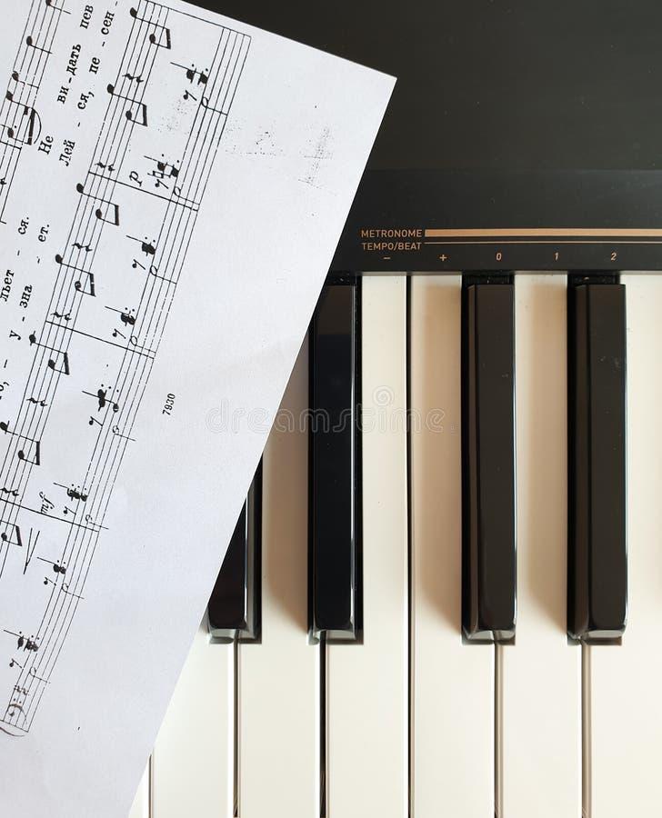 Brela 克罗地亚- Augest 5日2019年:乐器 与音乐纸张的黑白合成器键盘键 免版税库存照片