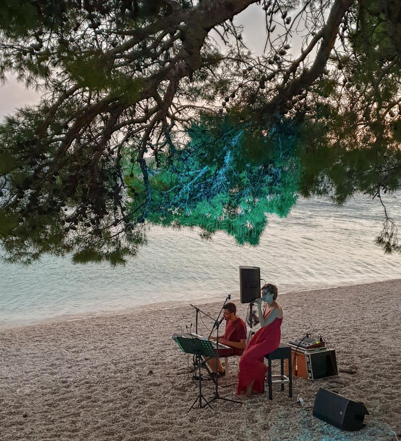 Brela. Croatia - June, 2019: live music on the beach.  A girl in a red dress sings a guy plays the synthesizer on a pebble beach royalty free stock photos