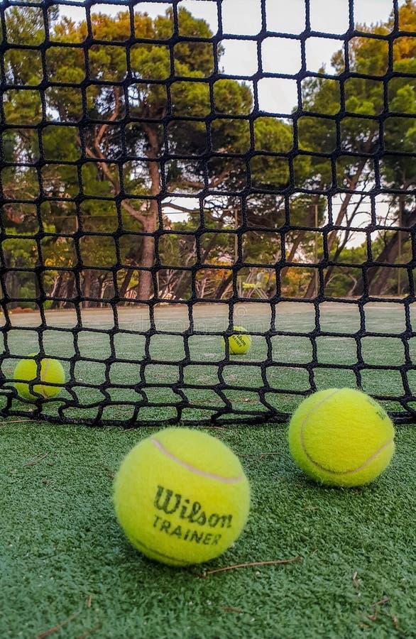Brela La Croatie - 9 août 2019 : balles de tennis sur une cour extérieure pendant l'été près du filet contre une forêt de pin image libre de droits