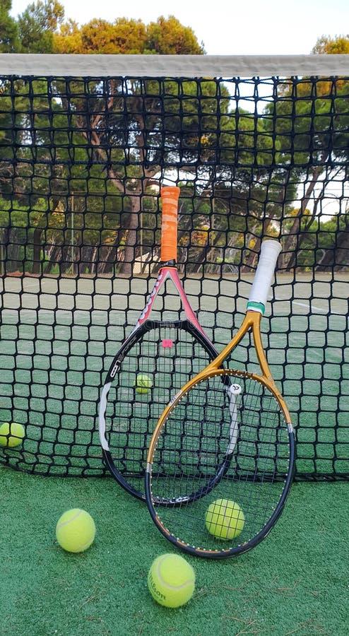 Brela La Croatie - Augest 9, 2019 : Raquettes et boules de tennis sur une cour extérieure en été près du filet contre une forêt d photographie stock libre de droits