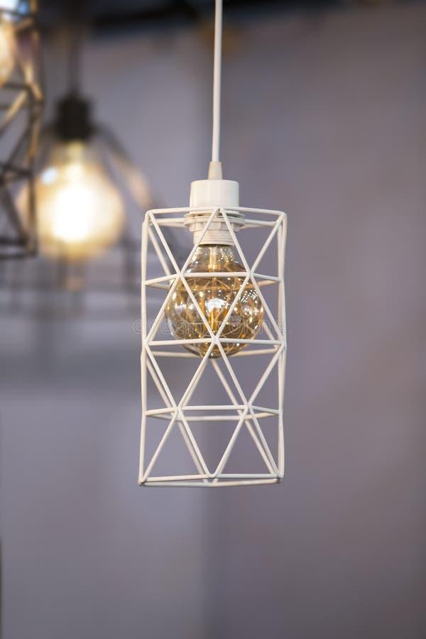 Breloczek lampy kształta geometryczny abażurek, białego metalu świecznik z złocistą lampą wśrodku Projekta loft fotografia royalty free