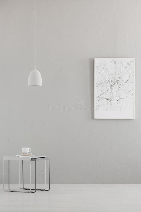Breloczka światło nad nowożytny stół, miasto mapy plakat na szarej ścianie w minimalistycznym żywym izbowym wnętrzu i miejsce dla fotografia royalty free