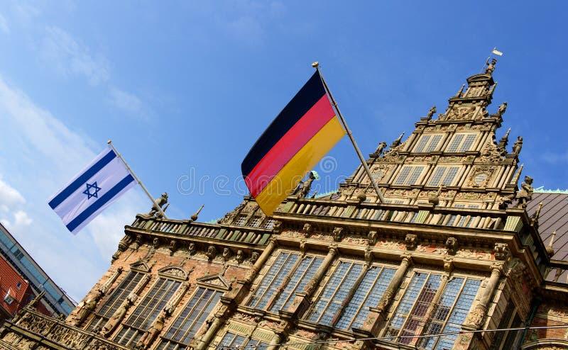 Brema, Alemanha - israelita e bandeiras alemãs que voam da câmara municipal histórica em honra da primeira visita do embaixador d imagem de stock