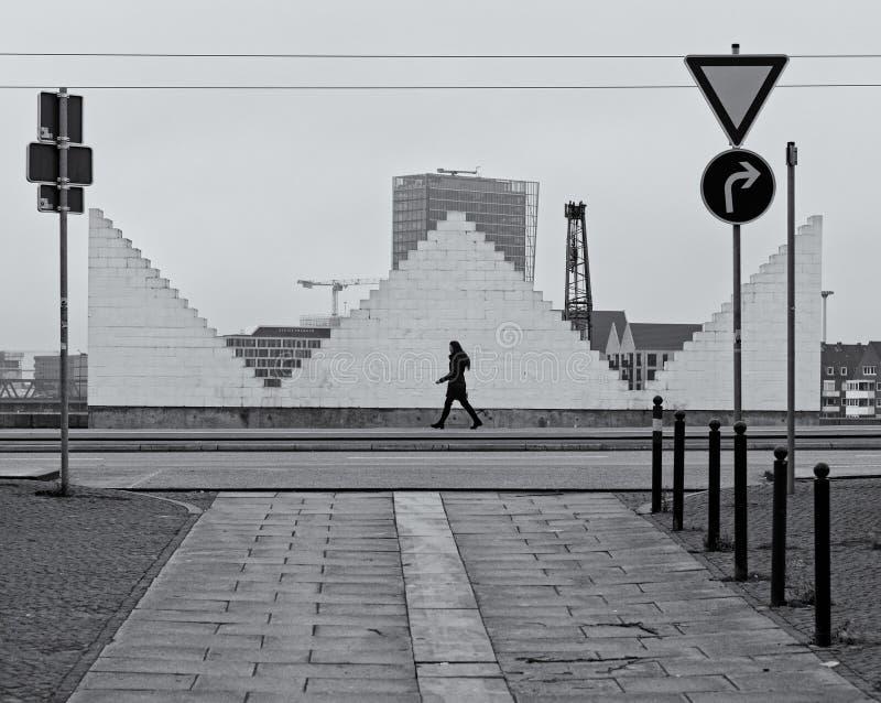 Bremen, Alemania - 31 de diciembre de 2018 - escena de la calle con la mujer solitaria que camina en una acera delante de una esc imágenes de archivo libres de regalías
