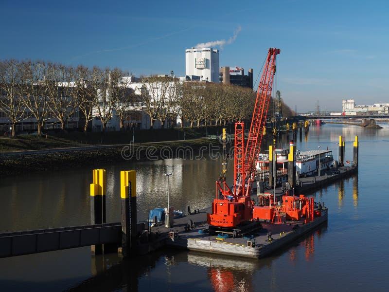 Bremen, Alemania - 14 de febrero de 2019 - embarcadero con varios pequeños buques y horizonte flotante rojo brillante de la grúa  imagen de archivo libre de regalías
