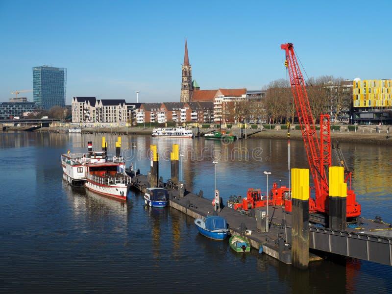 Bremen, Alemania - 14 de febrero de 2019 - embarcadero con varios pequeños buques y horizonte flotante rojo brillante de la grúa  fotos de archivo
