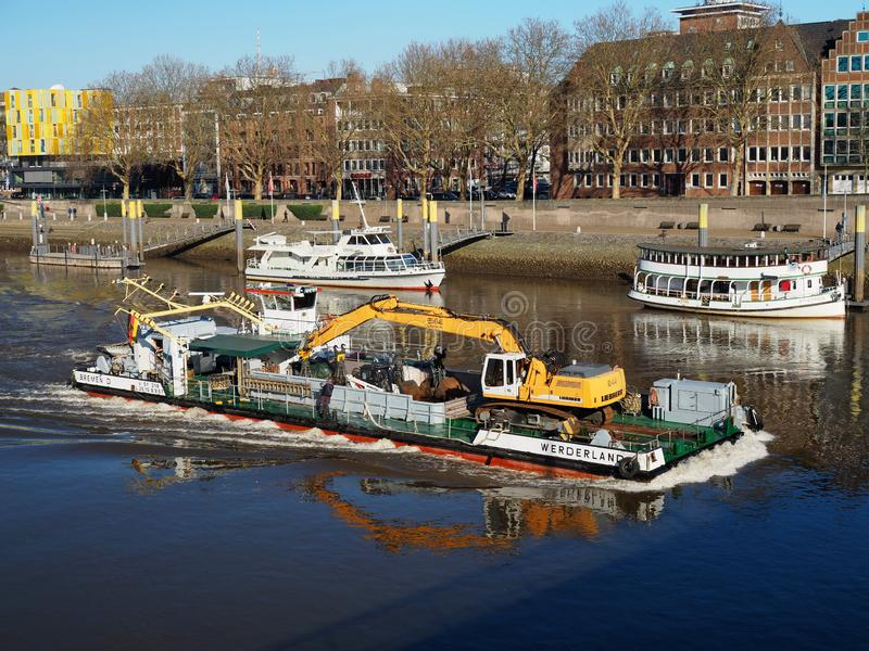 Bremen, Alemania - 14 de febrero de 2019 - gabarra que transporta una draga en el río Weser con los edificios y la orilla de la c foto de archivo libre de regalías