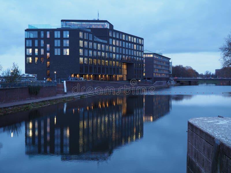Bremen, Alemania - edificio de oficinas del fabricante Enercon de la turbina de viento en la oscuridad que refleja en el agua imagen de archivo libre de regalías