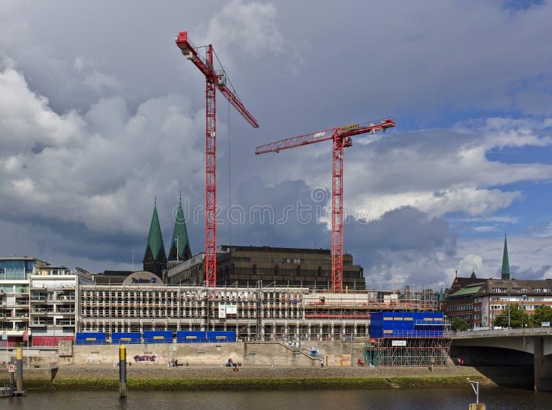 Bremen, Deutschland - 10. Juli 2018 - Baustelle des neuen Kuehne-Gebäudes auf der Bank des Flusses Weser mit enormen Kränen a lizenzfreie stockfotos