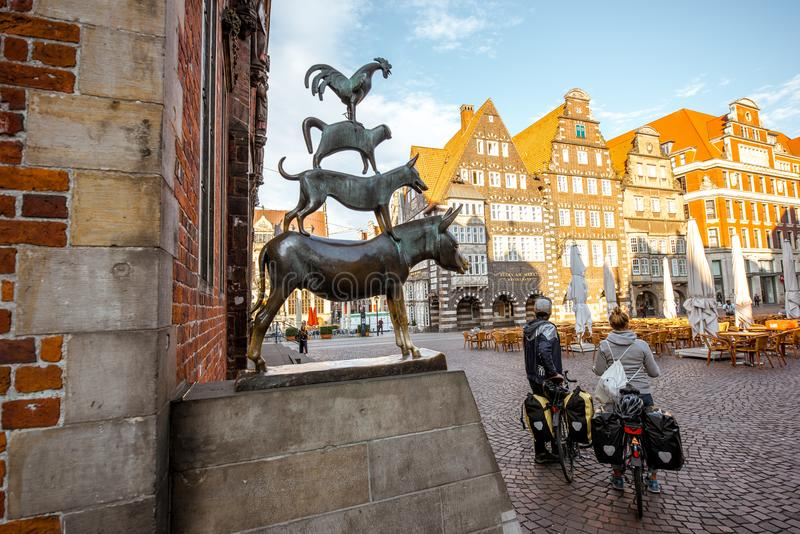 Bremen Musicians statue. BREMEN, GERMANY - August 10, 2017: Couple of tourist on the bicycles near bronze statue by Gerhard Marcks depicting the Bremen Town royalty free stock images