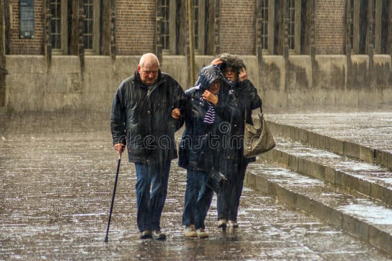 Bremen, Germany, 19 November 2017. Elderly people, passers-by in the pouring rain in the Central square of Bremen.  stock photo