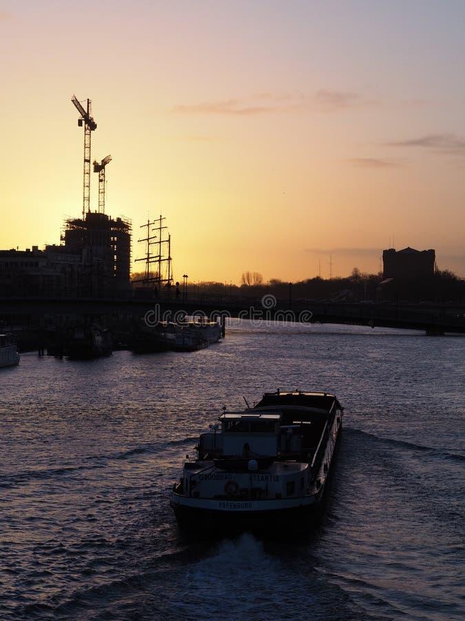 Bremen, Niemcy - ładunku statek na rzecznym Weser przy wschód słońca z budową i żurawiami w odległości fotografia stock