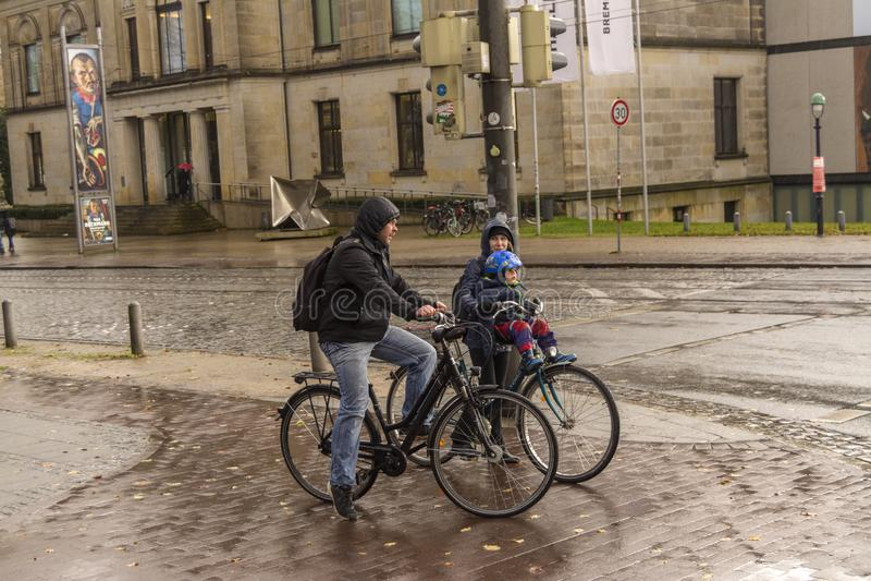 Bremen, Niemcy, 19 2017 Listopad Rodzina na bicyklach z małym dzieckiem na ulicach w deszczu zdjęcie royalty free
