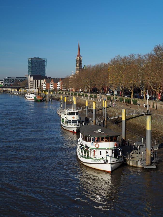 Bremen Tyskland - Februari 24th, 2019 - pir med flera förtöjde skyttlar med den Weser torn- och St Stephani kyrkan i arkivbild