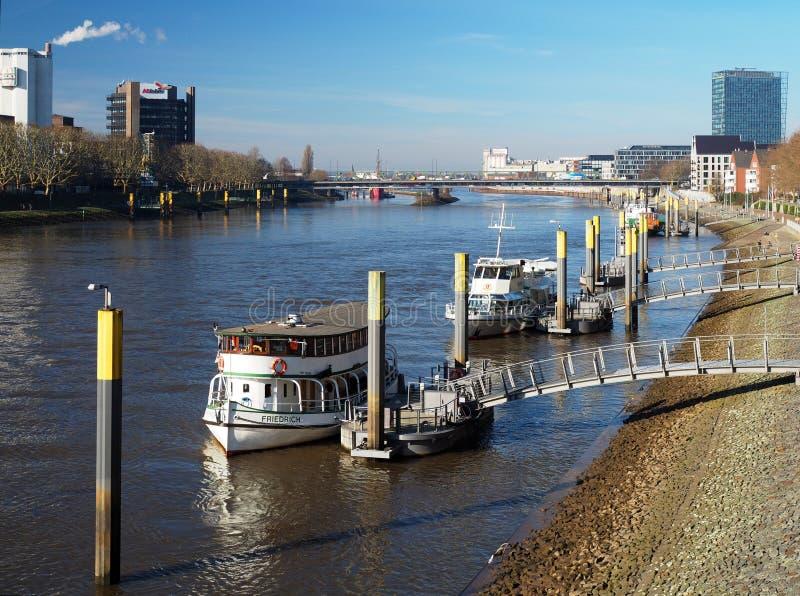 Bremen Tyskland - Februari 24th, 2019 - pir med flera förtöjde skyttlar med det Weser torn- och Beck bryggeriet i bakgrunden arkivbild