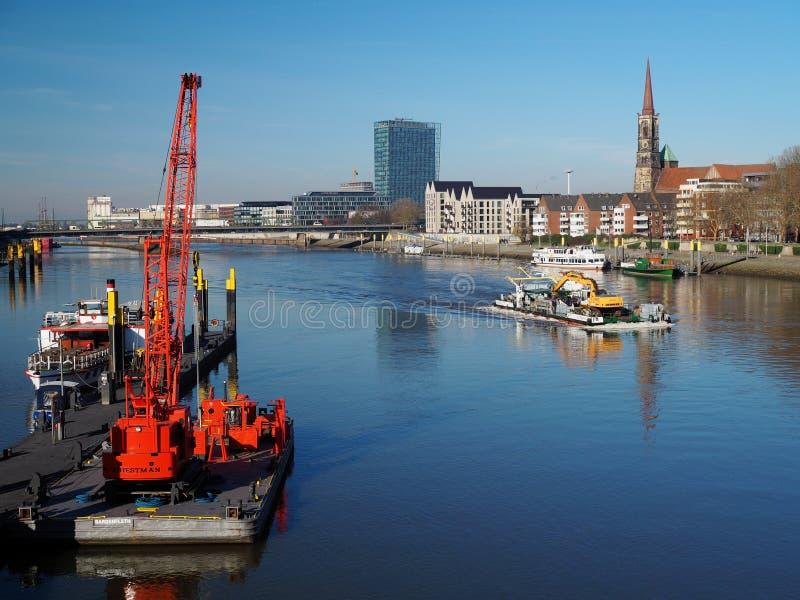 Bremen Tyskland - Februari 14th, 2019 - pir med flera små skyttlar och ljus röd sväva kran, pråm med dredgeren och stad royaltyfria foton