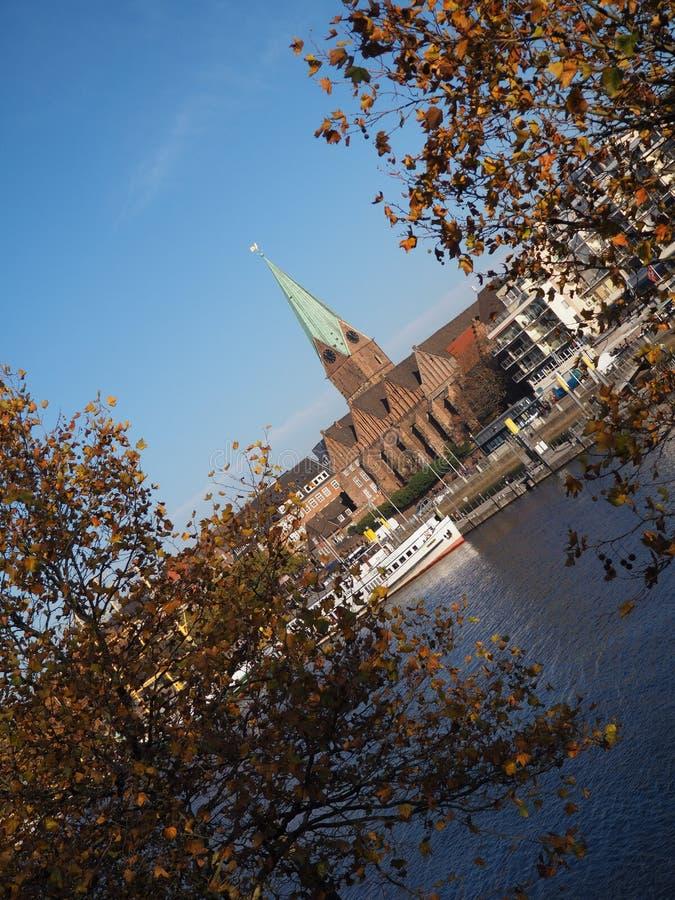 Bremen Tyskland - flod Weser med kyrkan för St som Martini inramas av träd i förgrunden med den lutade horisonten royaltyfri fotografi