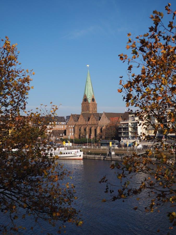 Bremen Tyskland - flod Weser med kyrkan för St som Martini inramas av träd i förgrunden med den lutade horisonten arkivfoto