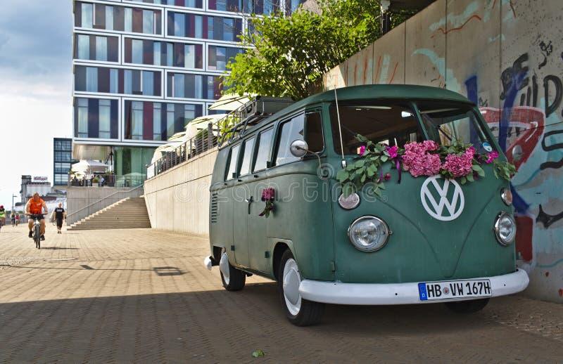 Bremen Tyskland - Juli 17th, 2018 - grön VW-T3-skåpbil med stor vitVW-logo med den moderna glass fasaden i bakgrunden royaltyfria foton