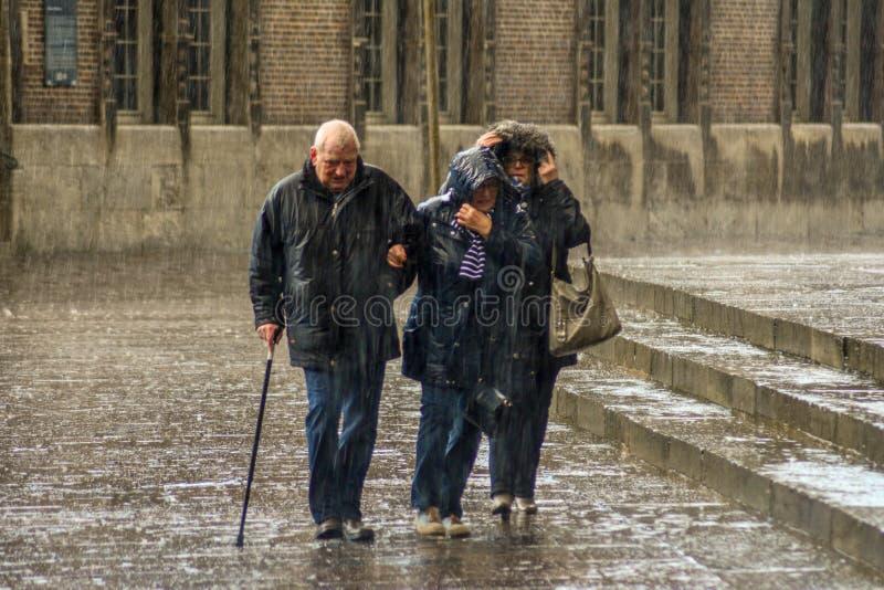 Bremen Tyskland, 19 November 2017 Äldre folk, förbipasserande i spöregnet i den centrala fyrkanten av Bremen arkivfoto