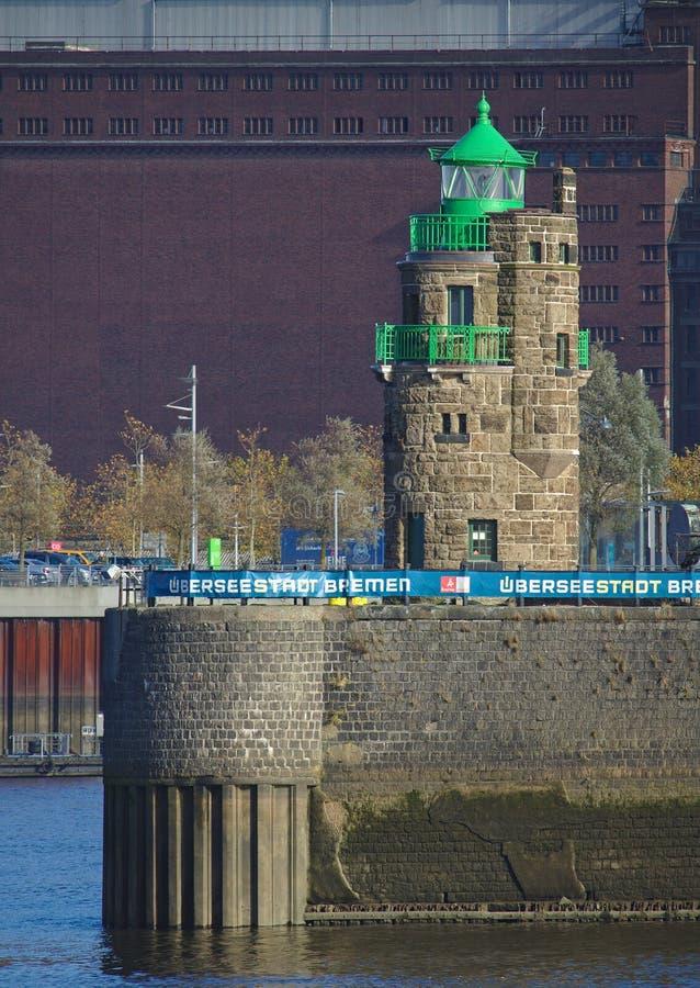 Bremen Tyskland - November 6th, 2017 - fyr på hamningången på en stenkaj med enorm historisk lagringsbyggnad i th arkivbilder