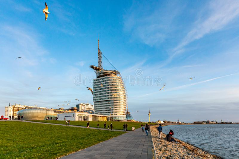 Bremerhaven, Germany - 2 Nov 2019: People playing with seagulls on Weser river Promenade am Strom riverfront embarkment in sunset. Sail-shaped Atlantic Hotel royalty free stock images