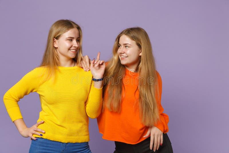 Brengt glimlachend jong blonde twee zustersmeisjes die in kleurrijke kleren samen elkaar bekijken die wijsvinger richten omhoog g stock fotografie