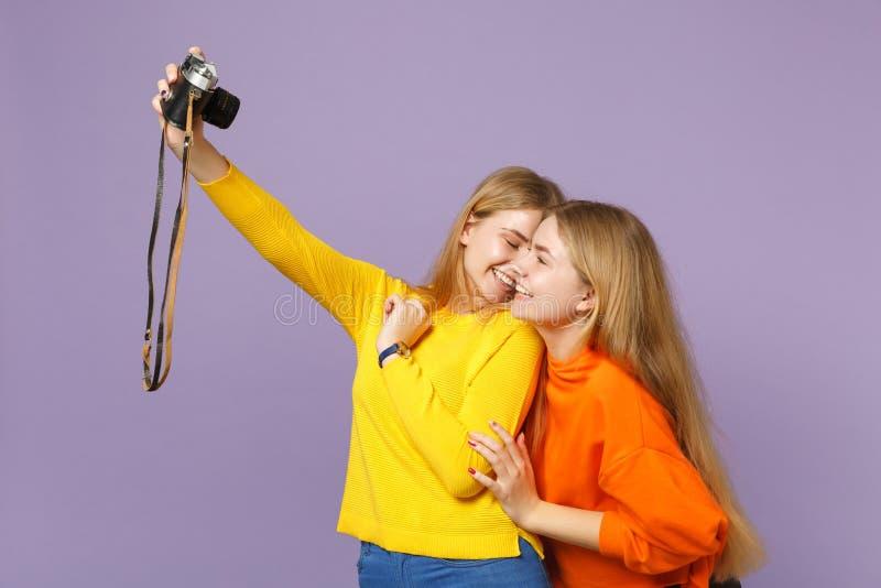 Brengt vrij jong blonde twee zustersmeisjes in het kleurrijke die kleren doen samen selfie op retro uitstekende fotocamera worden stock afbeelding